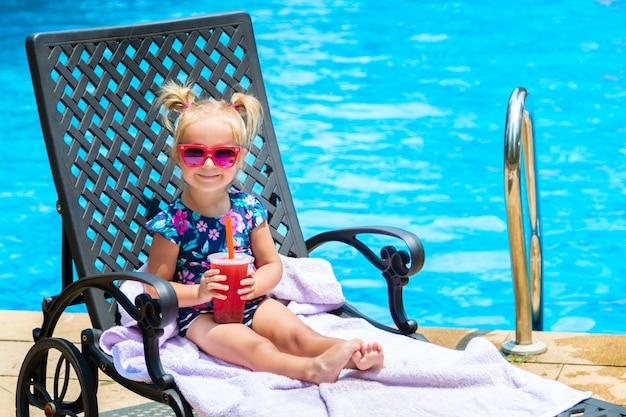Little girl in swimwear and sunglasses lying on lounger in swimming pool.