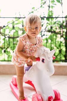 Little girl swinging on a toy unicorn on the balcony