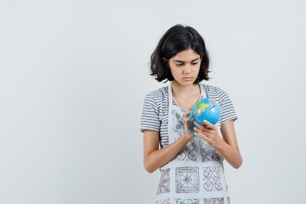 Little girl in t-shirt, apron choosing destination on school globe ,