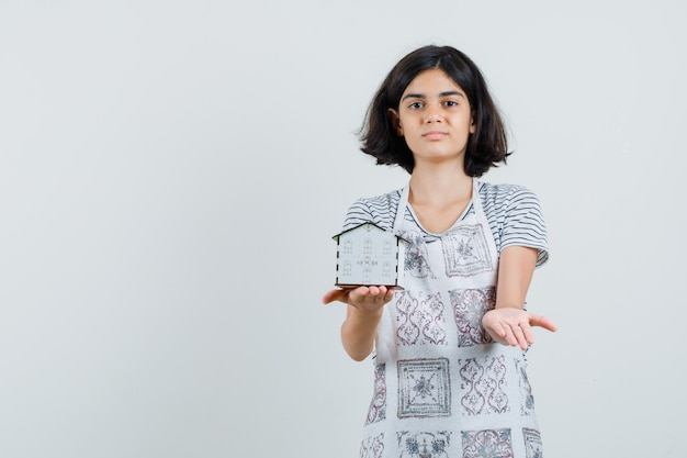 Bambina in t-shirt, grembiule che presenta il modello di casa e sembra sicura,