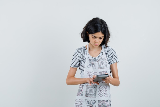 Little girl in t-shirt, apron using calculator and looking busy ,