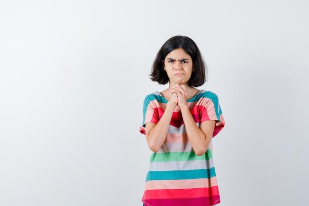 Bambina in maglietta che stringe le mani, fa una smorfia e sembra dispiaciuta, vista frontale.