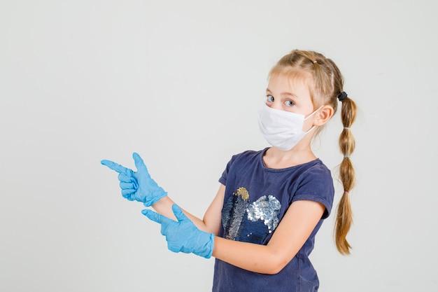 Bambina in maglietta, guanti e maschera che punta due dita guardando la fotocamera.