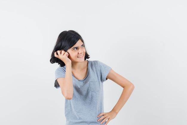 Bambina in t-shirt tenendo la mano sull'orecchio e guardando allegro, vista frontale.