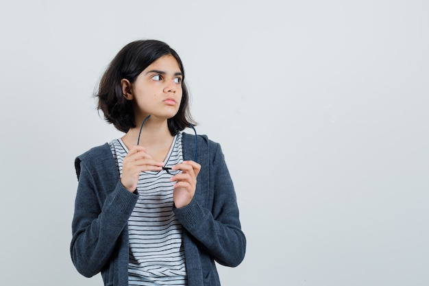 Little girl in t-shirt, jacket holding glasses and looking pensive ,