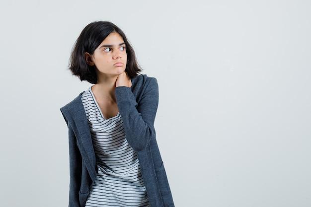Bambina in t-shirt, giacca tenendo la mano sul collo e guardando concentrato,
