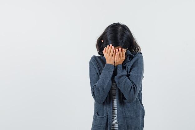 Bambina in t-shirt, giacca tenendo le mani sul viso e guardando depresso