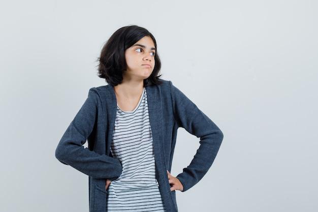 Bambina in maglietta, giacca che guarda da parte e sembra esitante,