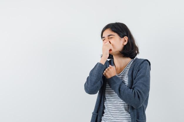 Bambina in maglietta, giacca che pizzica il naso a causa del cattivo odore e sembra disgustata,