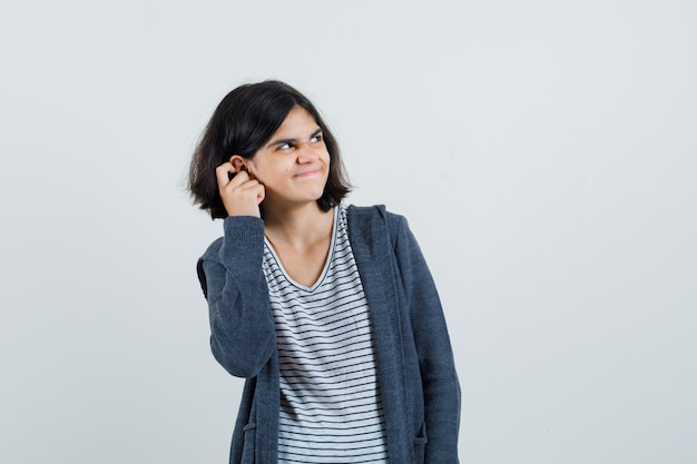 Little girl in t-shirt, jacket scratching ear and looking sorry ,