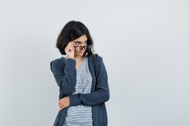 Little girl in t-shirt, jacket taking off glasses and looking amazed ,