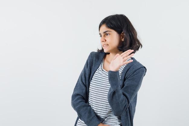 Bambina in t-shirt, giacca agitando la mano per dire addio e guardando allegra
