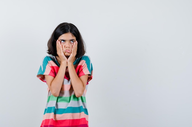Bambina in t-shirt, jeans che si tengono per mano sulle guance, distogliendo lo sguardo, facendo smorfie e guardando dispiaciuto, vista frontale.