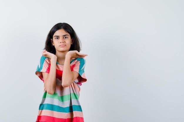 Bambina in t-shirt, jeans allungando le mani in modo interrogativo e guardando perplesso, vista frontale.