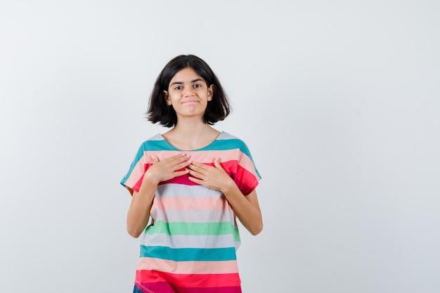 Bambina in t-shirt che tiene le mani sul petto e sembra allegra, vista frontale.