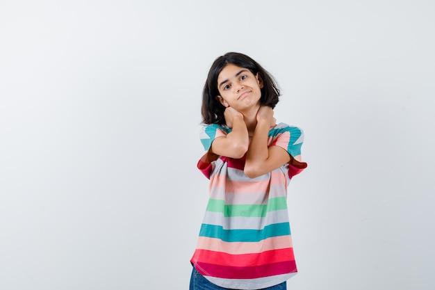 Bambina in maglietta che tiene le mani sul collo e sembra carina, vista frontale.