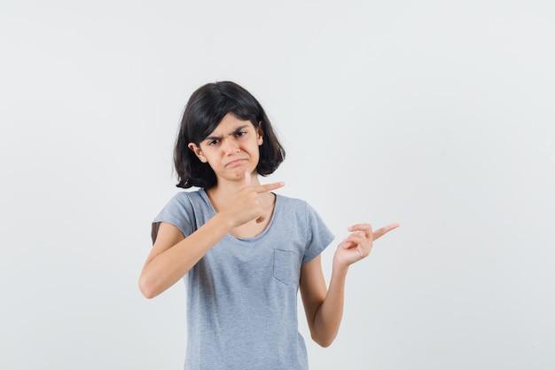 Bambina in maglietta che indica il lato destro e che sembra triste, vista frontale.