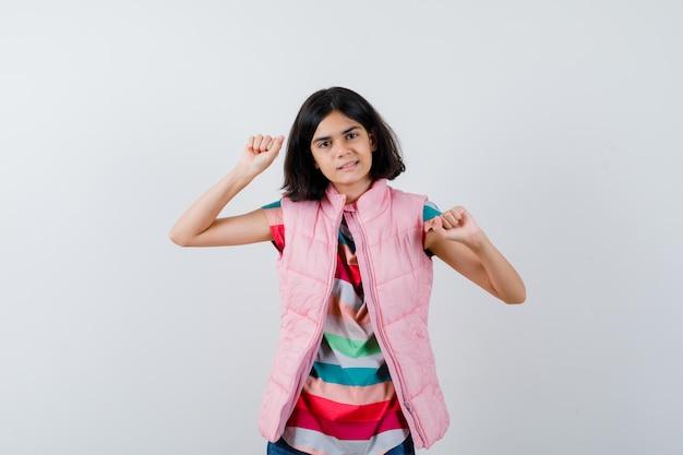 Bambina in t-shirt, gilet imbottito, jeans che mostrano il gesto del vincitore e sembrano felici, vista frontale.