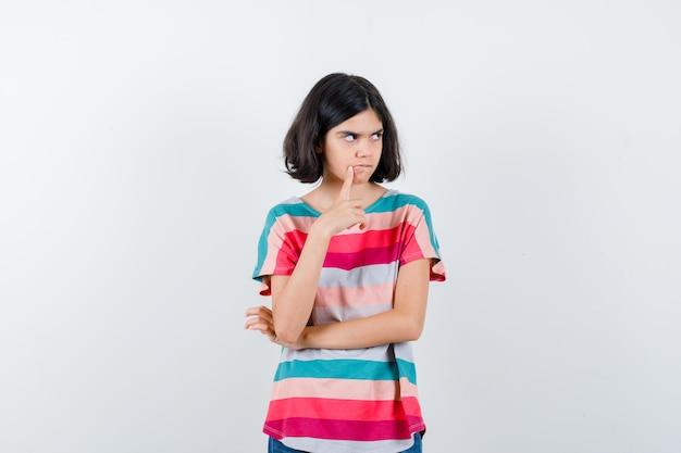 Bambina in maglietta che mette il dito indice vicino alla bocca, pensando a qualcosa e guardando pensieroso, vista frontale.