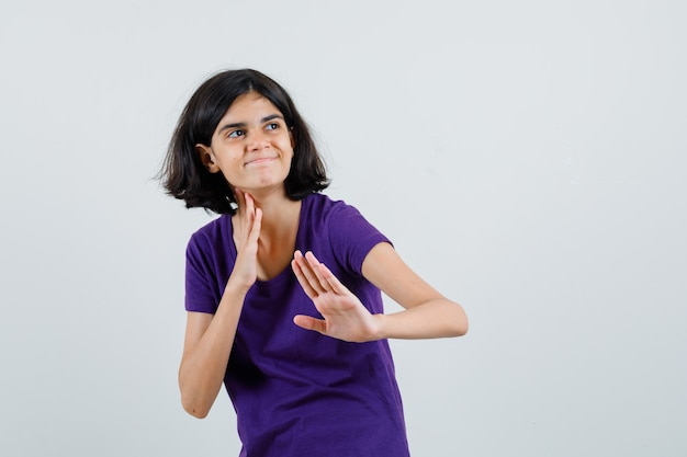 Little girl in t-shirt showing karate chop gesture and looking cheery ,