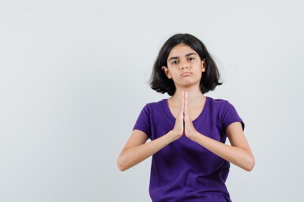 Bambina in maglietta che mostra il gesto di namaste e che sembra sconvolto,