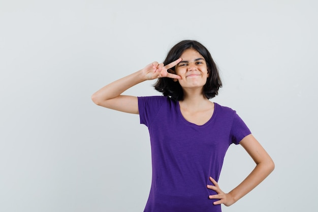 Bambina in maglietta che mostra v-segno vicino all'occhio e guardando divertito,