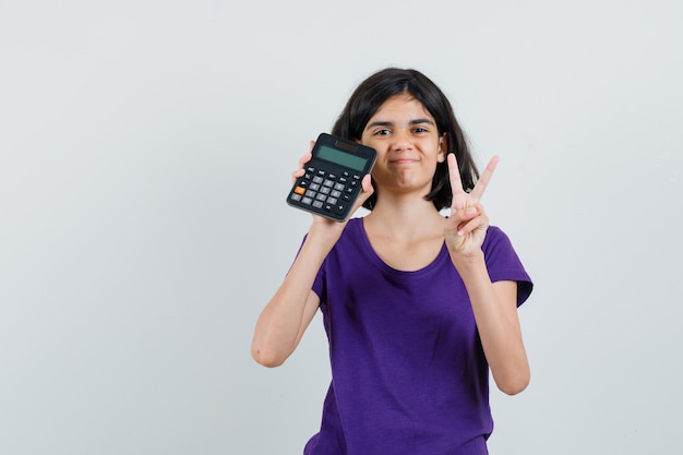 Little girl in t-shirt showing victory gesture, holding calculator and looking merry ,