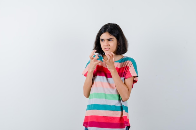 Bambina in maglietta che allunga le mani mentre tiene qualcosa e sembra infastidita, vista frontale.