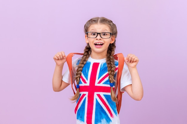 A little girl in a t-shirt with an image of the english flag on an isolated purple background. learning foreign languages.