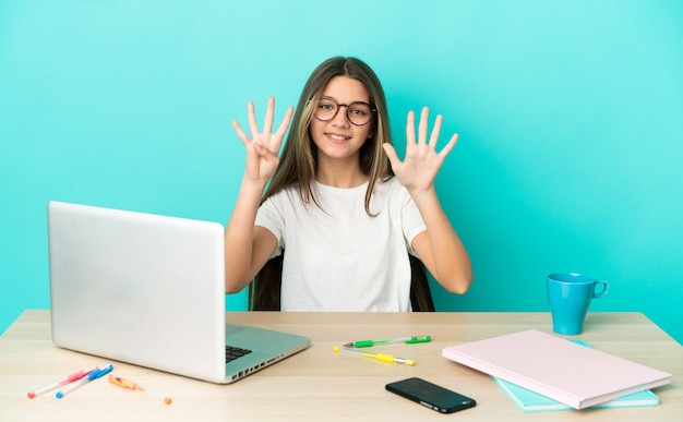 Little girl in a table with a laptop over isolated blue background counting nine with fingers