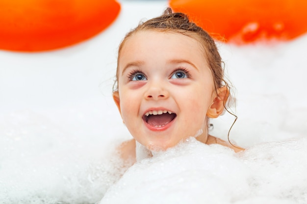 Little girl takes a bath in a hydromassage bathtub.