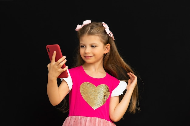 A little girl takes a picture of herself on her phone.