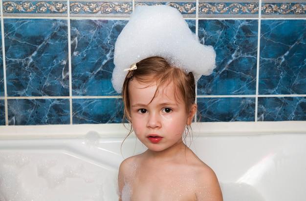 거품 목욕을 하는 어린 소녀. 건강 관리 및 위생 개념입니다.