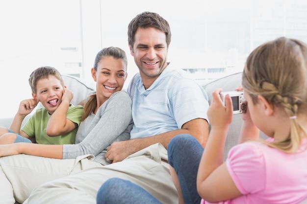 어린 소녀는 소파에 그녀의 가족의 사진을 복용