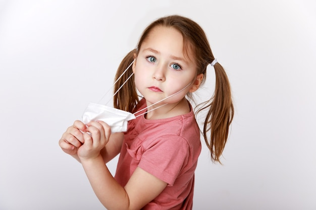 Маленькая девочка снимает медицинскую маску, чтобы лучше дышать