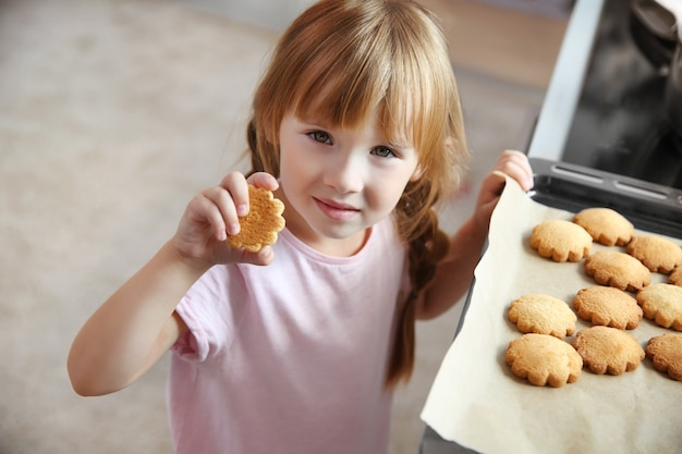 Little girl taking biscuits from baking tray