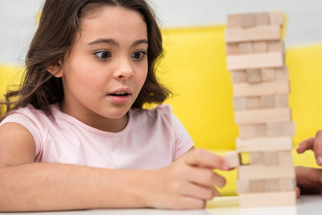 Little girl taking care while getting a piece of a wooden tower game