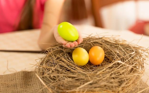 Little girl taking easter egg from the nest
