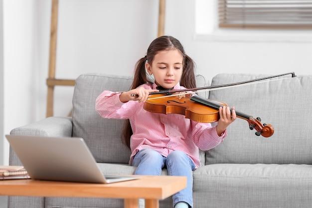 집에서 온라인 음악 수업을받는 어린 소녀