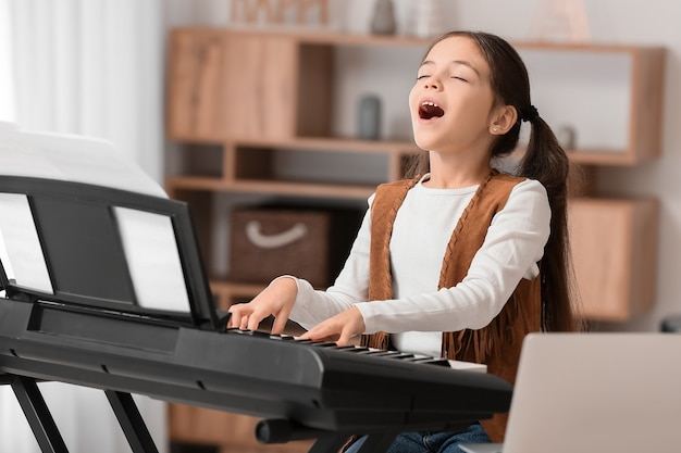 自宅でオンラインで音楽のレッスンを受けている少女