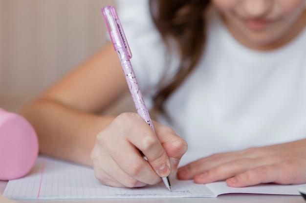 온라인 수업에 대 한 메모를한다는 어린 소녀