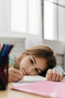 Little girl taking notes while being bored