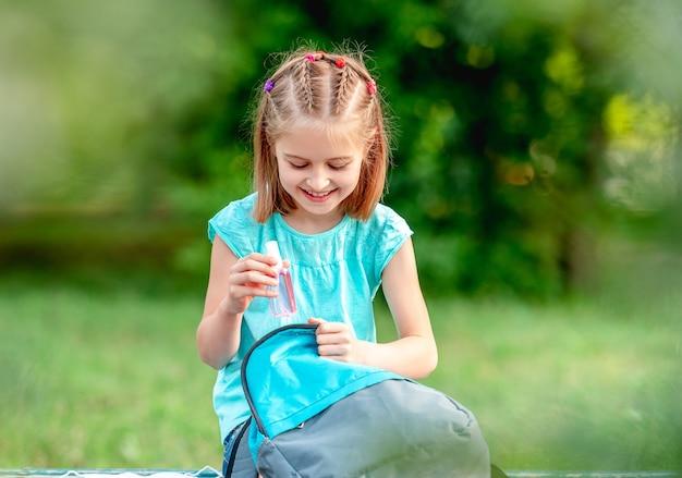 Маленькая девочка вынимает медицинскую маску из рюкзака в парке