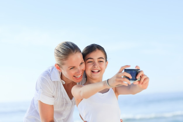 Little girl taking a photo of herself and her mother