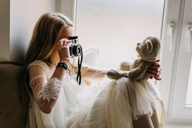 Маленькая девочка фотографирует плюшевого медведя со старой камерой