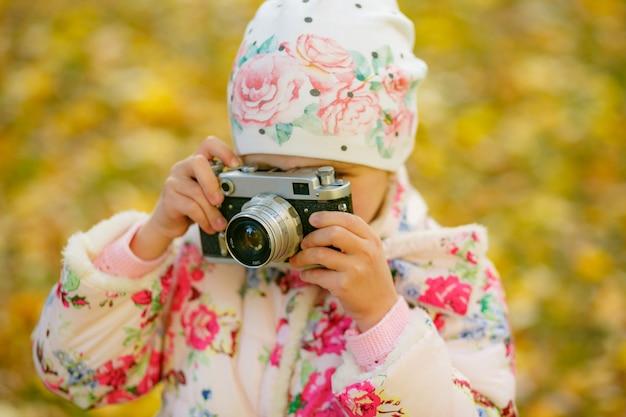ビンテージフィルムカメラを使用して写真を撮る少女