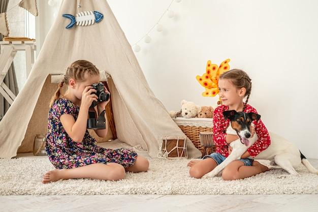 プレイルームの床に座っているフォックステリア犬を抱いて友達の写真を撮る少女