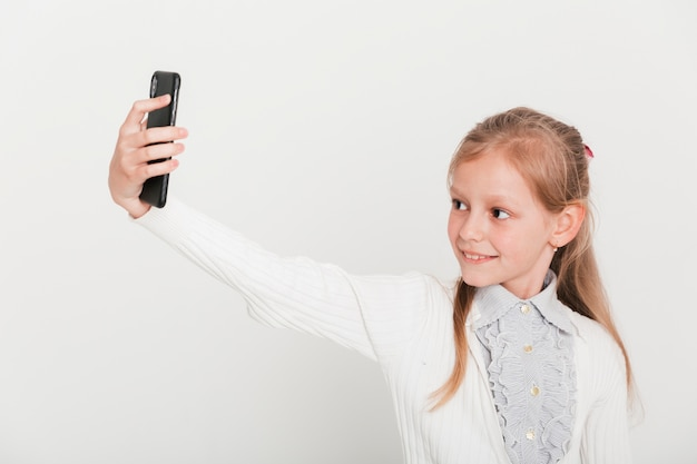 Little girl taking selfie with smartphone