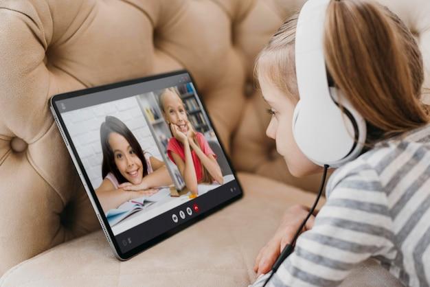 Bambina che parla con i suoi amici su un laptop in videochiamata