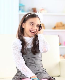 Маленькая девочка разговаривает по телефону.